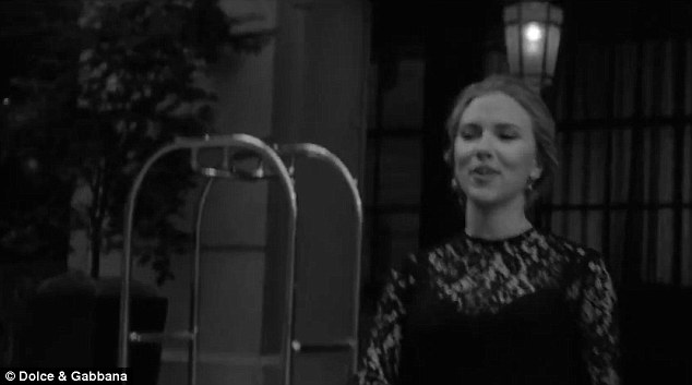 Pick up: Scarlett waits to be picked up outside her hotel wearing a classic lacy black dress