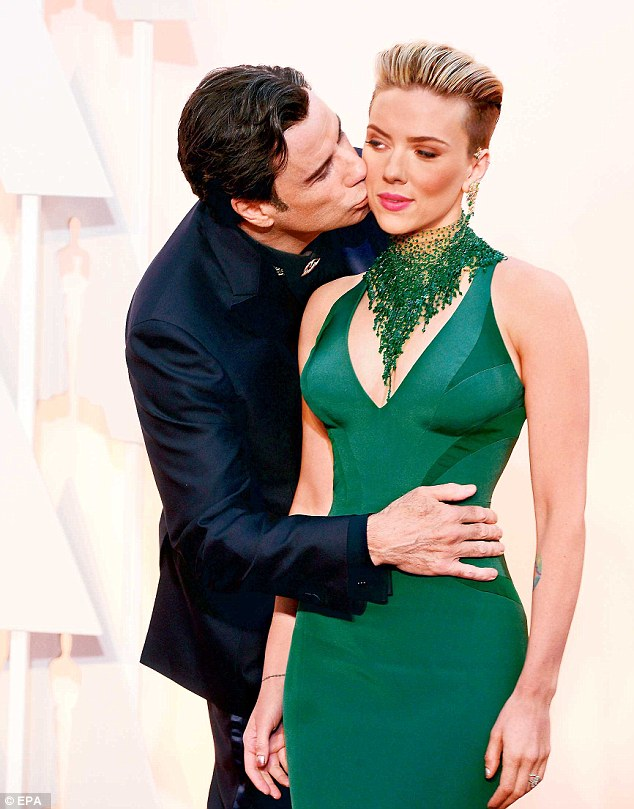 Sneak attack: Actor John Travolta, who fluffed Frozen singer Idina Menzel's name at last year's Oscars, grabbed all the social media heat again by sneaking up on Scarlett Johansson on the red carpet