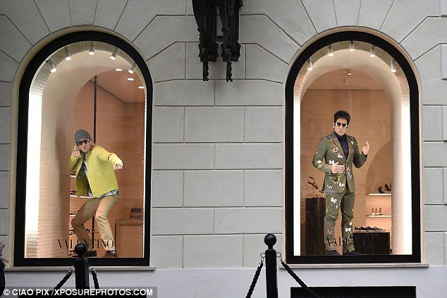 Duo: Ben looked dapper in a khaki coloured suit covered with butterflies as he struck a pose in the swanky Valentino shop window in Italy on Sunday afternoon