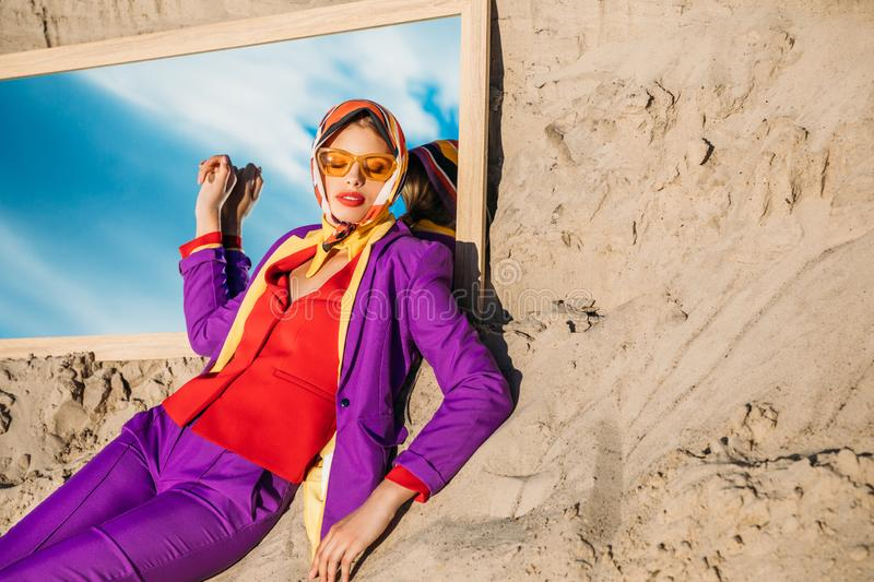attractive fashionable woman in stylish clothes lying on sand and mirror with reflection stock photo