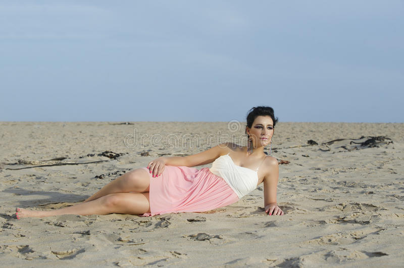 Beautiful woman in feminine dress lying in sand of desert stock photos