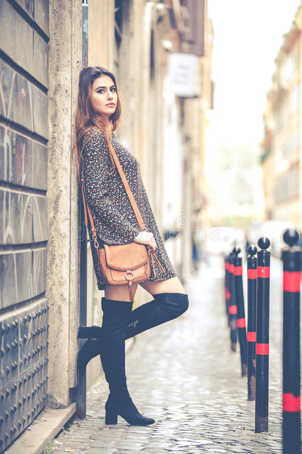 Beautiful woman outdoors in the city. Fashion and youthful charm. Woman with her purse, dress and boots in the historic center of Rome, Italy royalty free stock photography