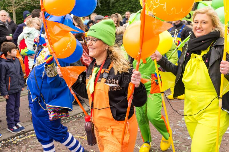 Cheerful lady in orange overall with green hat holds a stick with orange balloons royalty free stock images