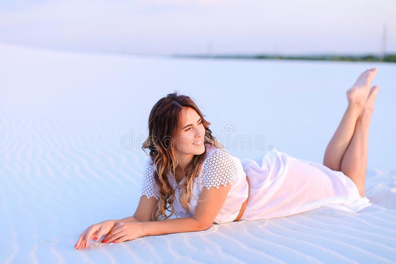 Charming caucasian woman wearing white dress lying on sand in su royalty free stock images