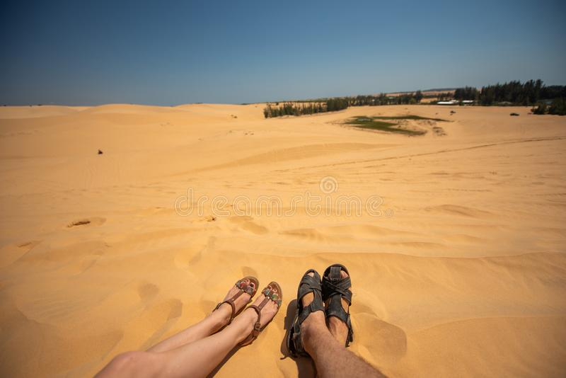 Close up portrait of legs, legs of couples lying with a mixture of golden sand dunes.Feet of a man and a woman in stock images