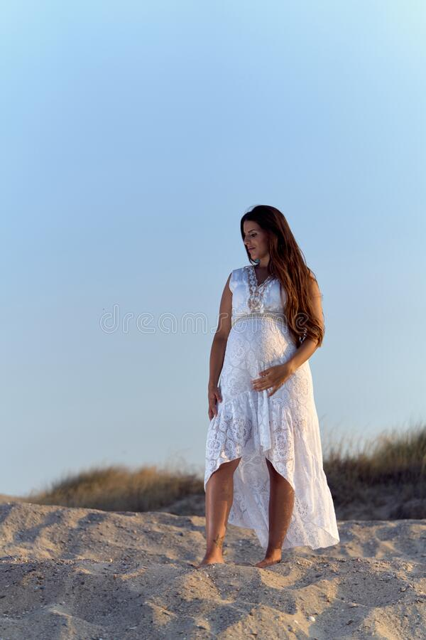 Pretty young pregnant woman with bare feet on the sand royalty free stock photography