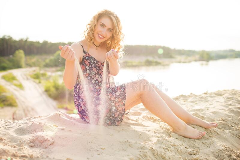 Pretty young woman plays on the sand stock image