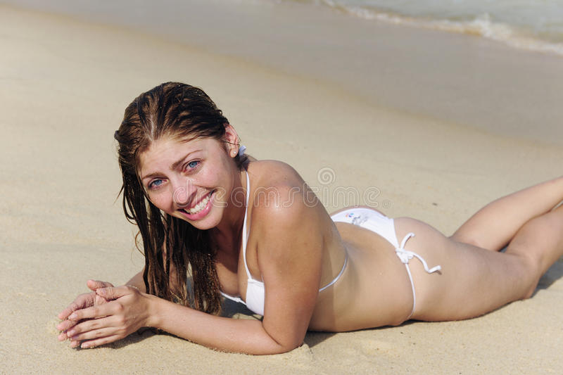 young woman lying in the sand on the beach stock images