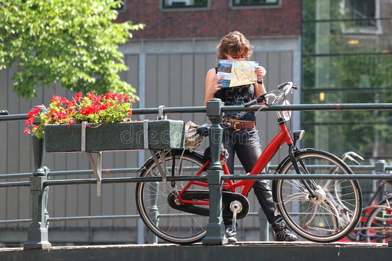 Tourist with map and bicycle. Amsterdam, Netherlands. stock photos