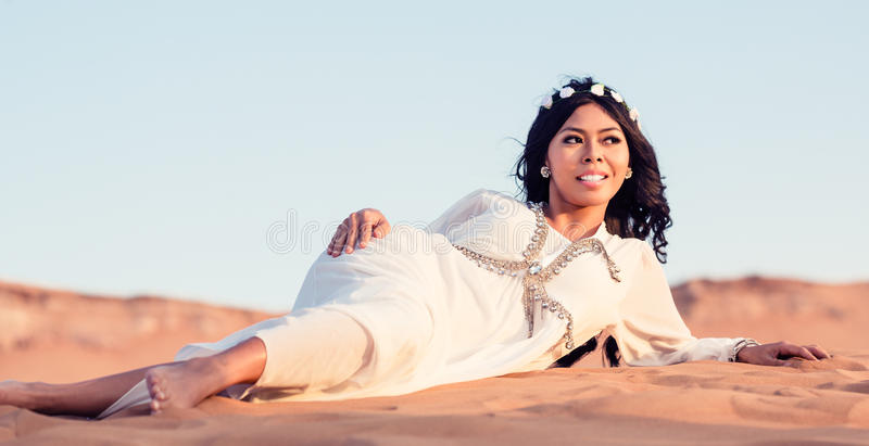 Woman laying in sand of Arabian desert stock photography