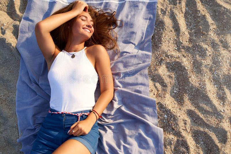 Young tanned pretty woman laying in the sun on beach towel. Attractive stylish fashionable female lies on warm sand and stock photo