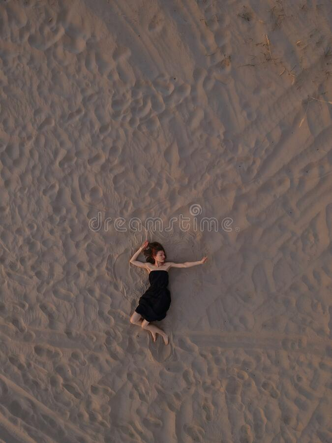 Young woman in a black dress lying on the back on the sand. Top view from the drone stock images