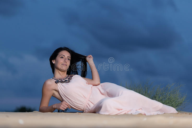 Young woman lying on a sand dune royalty free stock photos